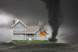 Picture of a house burning with a tornado next to it