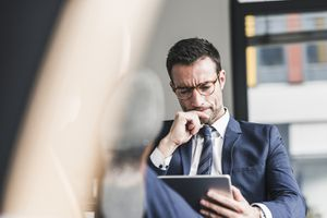 Businessman Using Digital Tablet, Sitting in Office With Feet Up