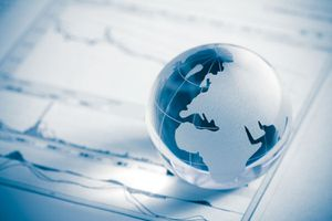 A small globe on top of a stock market chart.