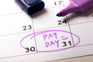 Payday concept calendar with marker and circled day of salary.