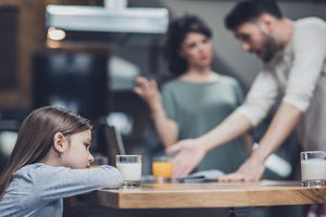 Parents argue while a little girl sits at a table with a glass of milk