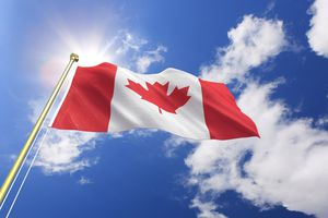 A Canadian flag waving in the wind on a sunny day