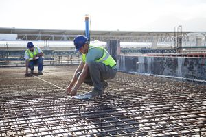 Construction workers arranging rebar at construction site