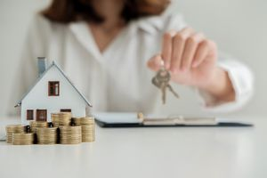 A woman holding house key with coins and a little house.