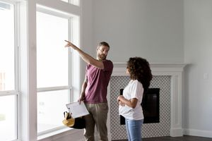 Home inspector points to something outside while talking with homeowner