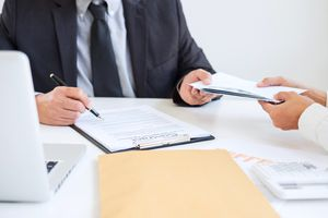 Businessman Receiving Envelope From Colleague