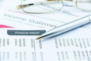 Blue ballpoint pen on a quarterly corporate financial report.