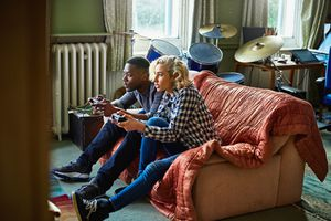 Two young adults playing console video games sitting on a couch in a small apartment.