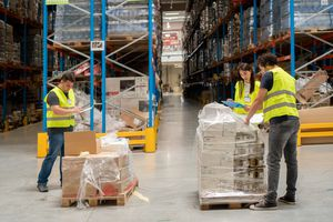 A group of workers moving boxes in a warehouse