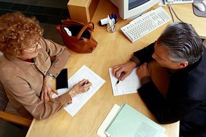 Older man and woman at a desk with papers