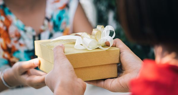 Close-Up Of Woman Giving Gift Box To Friend