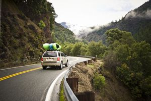 Car with Kayaks Driving Windy Road in Mountains