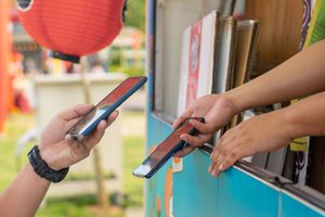 hand holding smartphone and scanning the barcode for contactless payment at the food truck