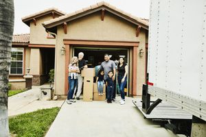 Portrait of smiling multigenerational family standing in front of new home on moving day
