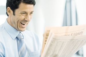 Businessman looking at newspaper excitedly.