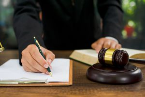 Midsection of a lawyer writing on a clipboard with a book open and a gavel and block on the table