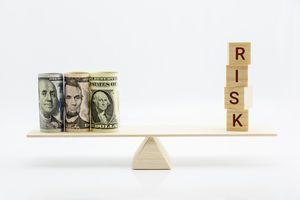 Dollar bills and risk wood blocks on a basic balance scale.
