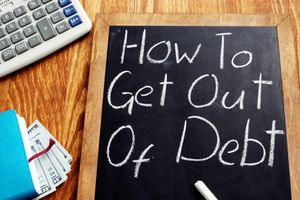 How to get out of debt handwritten on a blackboard.