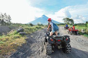 Rear View Of Woman Riding Quadbike On Dirt Road