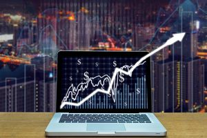 Stock exchange market trading graph over the screen of computer laptop on wood table over the photo blurred of trading graph background, business marketing trade concept