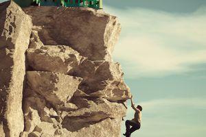 A man climbing a rock face toward a house