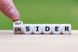 Hand turns a dice and changes the word 'OUTSIDER' to 'INSIDER' (or vice versa).