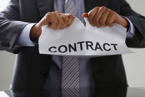 A white collar worker in suit and tie tear contract.