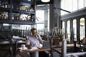 Senior business restaurant doing paperwork at laptop
