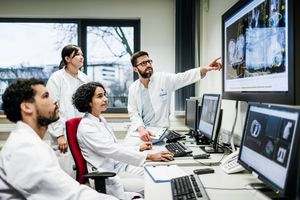 A team of doctors looking at some lab results together on monitors.