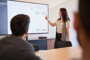 A businesswoman using graphs on a screen in business meeting.