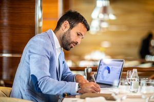 Entrepreneur Writing on a Document While Sitting in a Restaurant