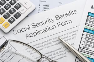 A Social Security application with calculator, eyeglasses, and pen.