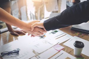 Two people shaking hands over financial documents