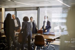 Smiling professionals shaking hands in a conference room