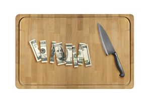 Knife and sliced hundred dollar on Wooden cutting board