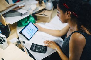 Small business owner using tablet while calculating finances