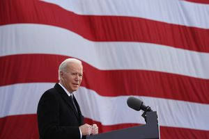 President Biden at microphone in front of an American flag
