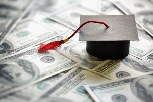 A graduate cap on top of hundred dollar bills