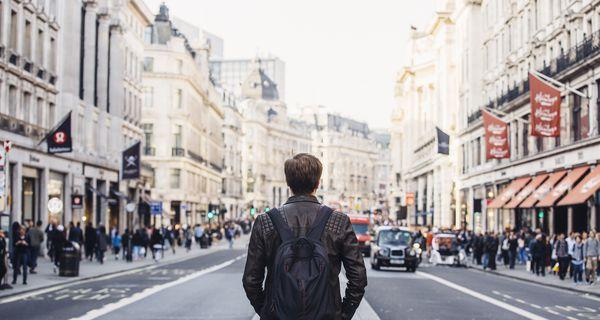 Tourist with backpack walking on Regent Street in London, UK.