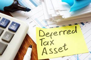 Deferred tax asset handwritten sign and calculator.