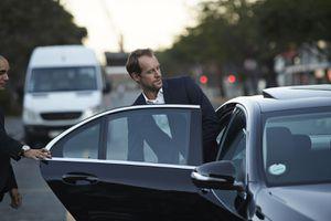 Driver assisting businessman into cab