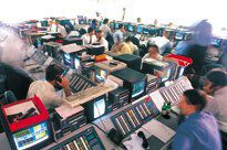 Traders sitting at terminals in a large room