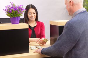 A bank customer making a financial transaction with a bank teller.
