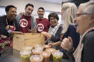 Playful Volunteers Packing Soup Containers in Crate in Soup Kitchen