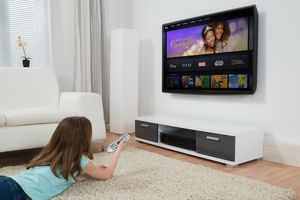 A young girl lying on a mat while watching a kids movie on the Disney Plus streaming service on a TV,