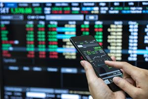 A businessman checking stock market data using a mobile phone.