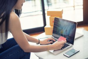 Young Woman Paying Shopping Online With a Credit Card at Home