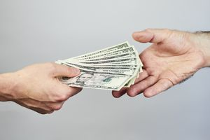 Two hands exchanging dollars on grey background.
