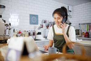 Bakery business owner talking on cell phone.