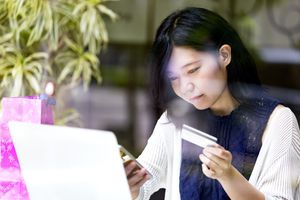 woman looking at computer and credit card information